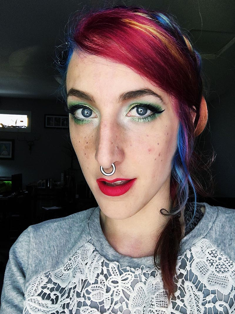 stephanie has rainbow hair and saturated green eye makeup, with hot pink lips