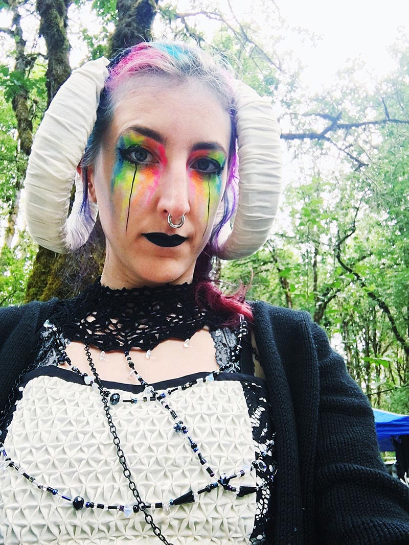 stephanie wearing horns, a lace costume, and neon rainbow dripping makeup