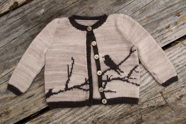 a cream colored knit baby sweater with a dark brown sillhouette of a bird on a branch in intarsia