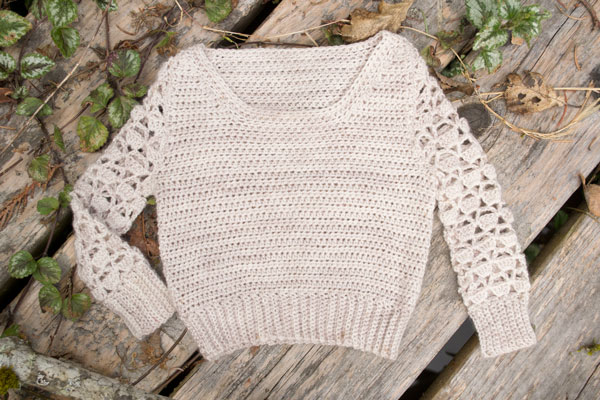 a cream colored crocheted baby sweater with lace sleaves