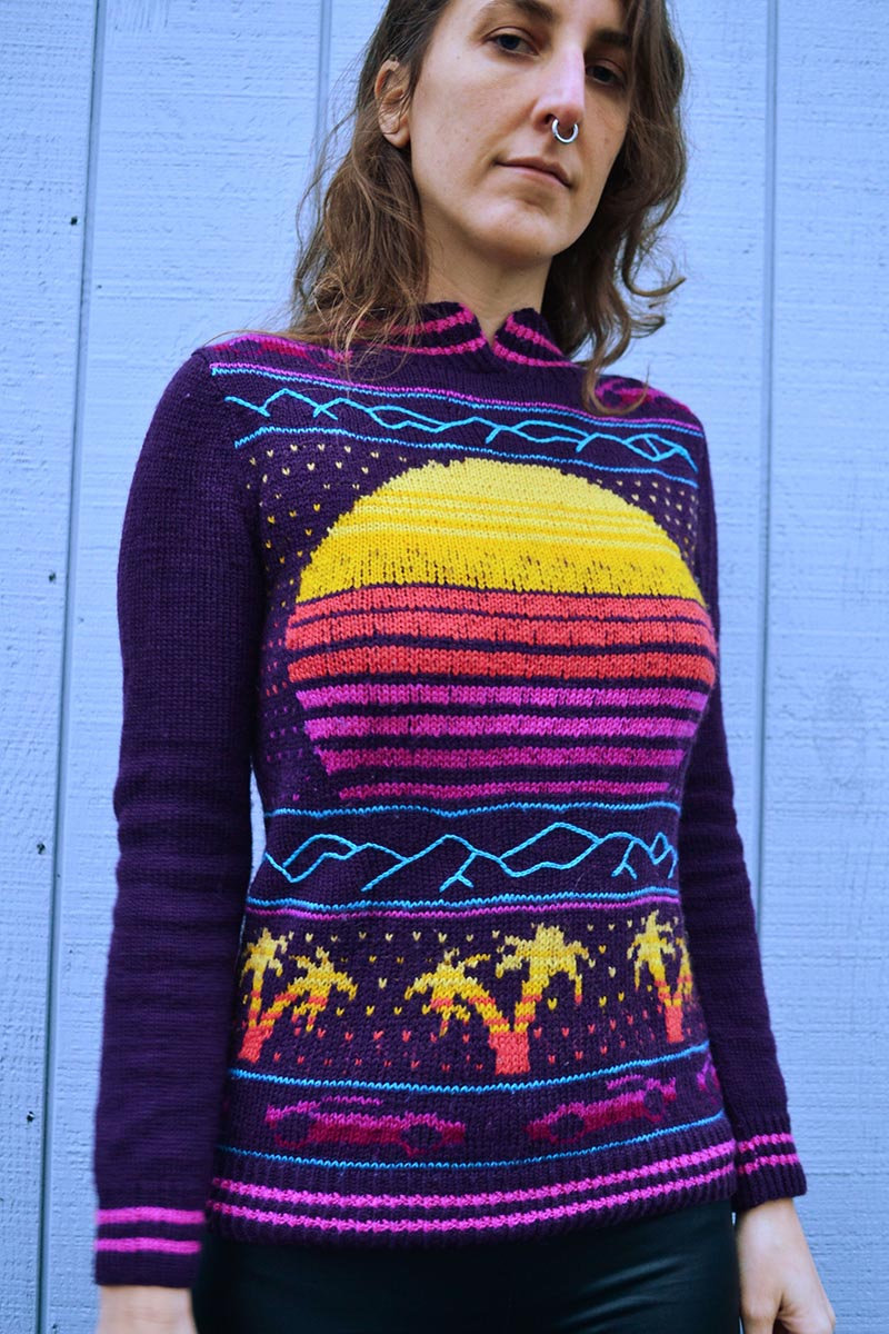 knit sweater with outrun motifs, including a setting sun, palm trees, and ferraris