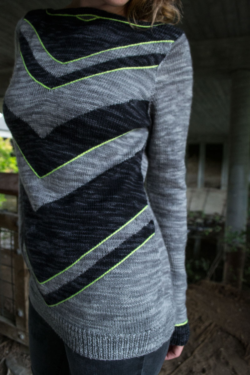 a long sweater featuring chevrons on the front and visible shaping on the back