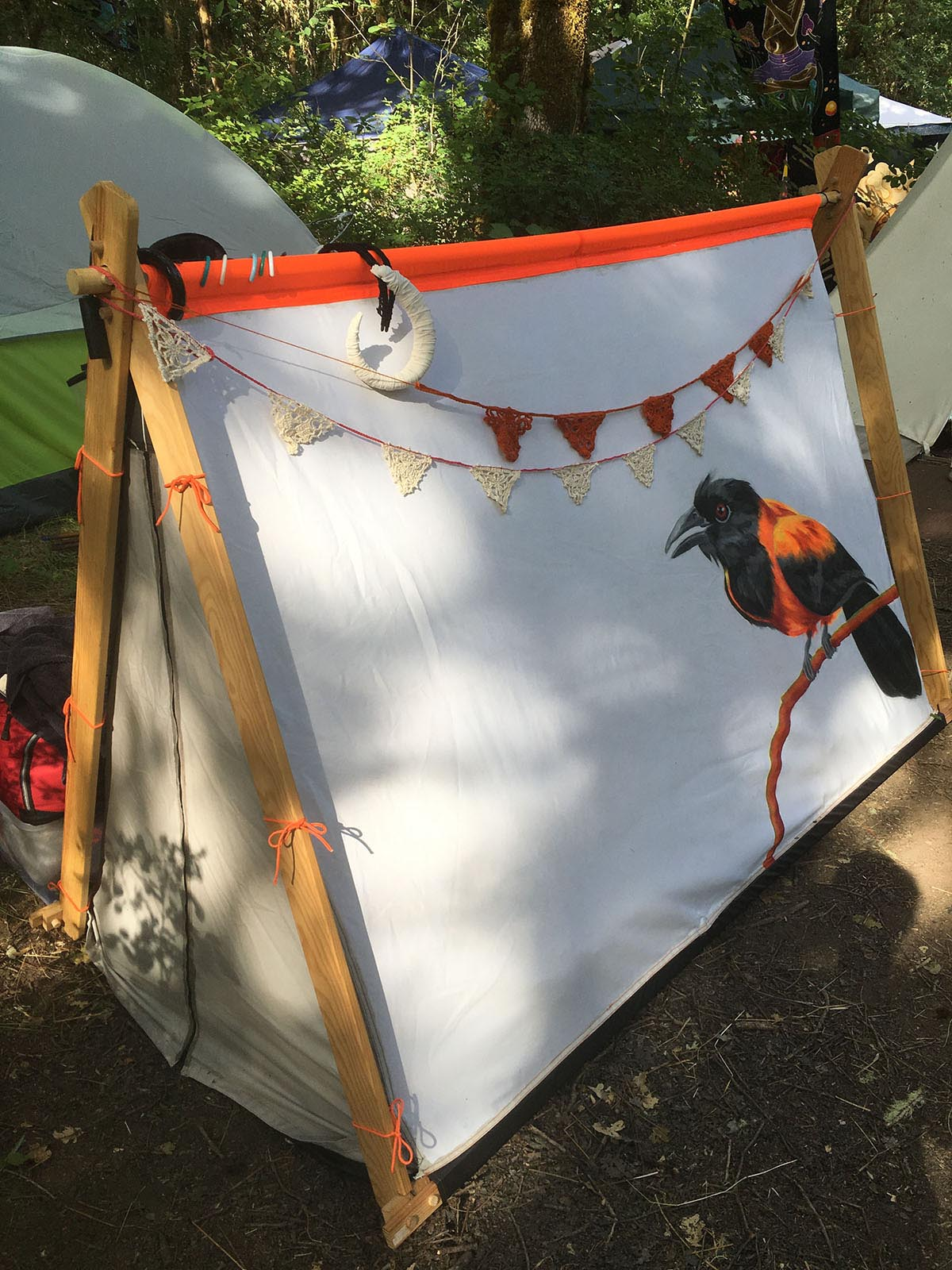 an aframe tent with the bird painting, with crocheted buntings hanging across